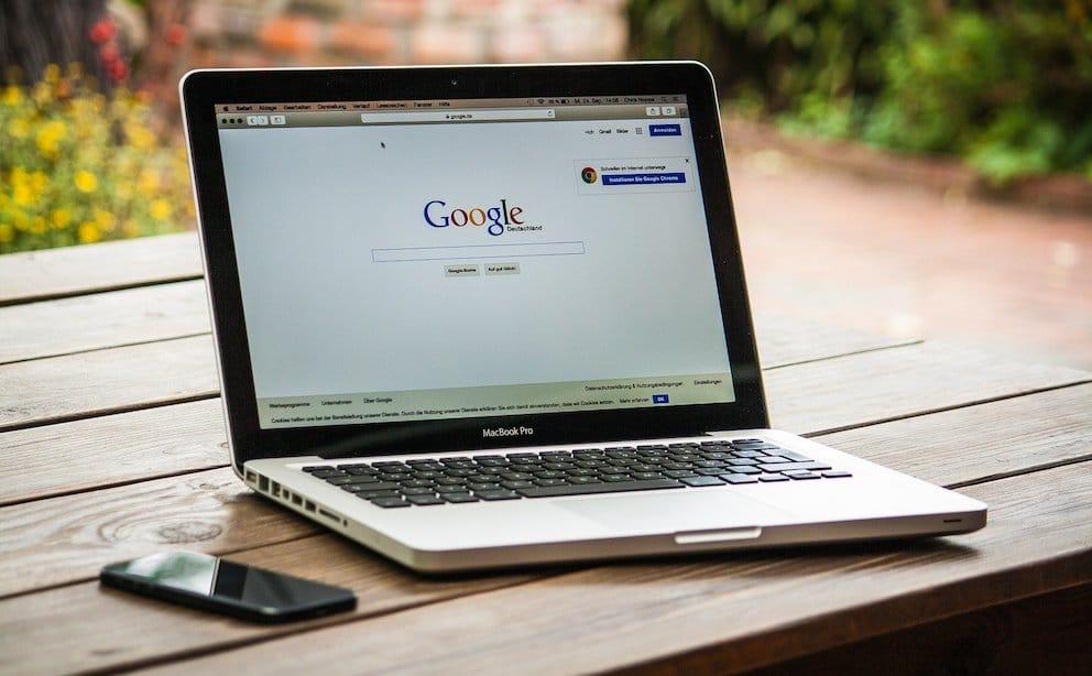 Création de site internet personnalisé. Un ordinateur portable posé un une table et un smartphone posé à sa gauche